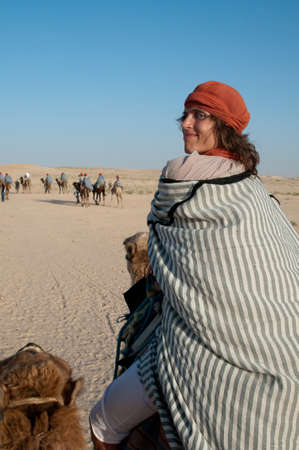 guise: This is a journey on camel in Sahara Desert. The woman dressed in bedouins guise turned round and smile.   Stock Photo