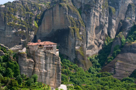 The Holy Monastery of Rousanou or St. Barbara is one of Meteora rock pillars in Greece. This is good combination of ancient architecture and mountain landscape. photo