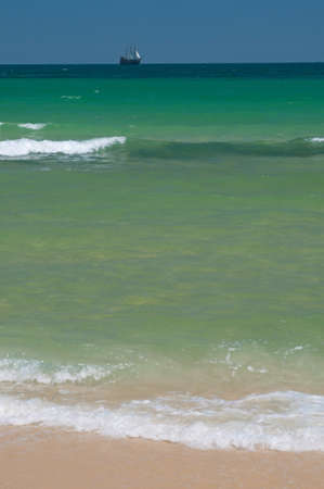 Emerald-green waves creep to the sand  Jackass brig with white sails is seen on the horizon  photo
