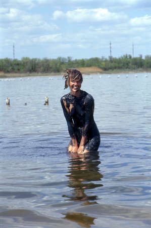 mud woman: This is the Monaky lake  Yevpatoria, Crimea  containing therapeutic muds  Young woman takes a mud cure