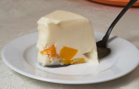 This is a wedge of jelly cake  The cake contains cream and peaches  photo