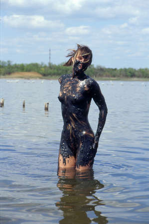This is the salt lake containing therapeutic mud  Young woman takes a mud cure