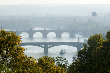 This is a morning view of the bridges on the Vltava River in Prague, Czech Republic  Two tourists do a famous town from the aerostat