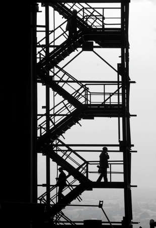 People is moving up and down the stairs of the industrial project  The metallurgical production dominate the town