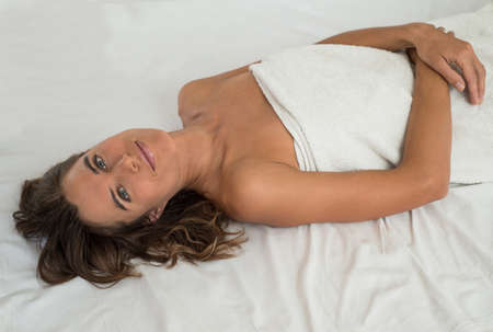 Woman is lying on the white bedsheet  She is  wrapped in a white towel  photo