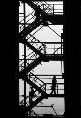 metallurgical: People is moving up and down the stairs of the industrial project  The metallurgical production dominate the town  Stock Photo