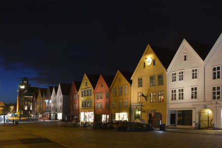 This is illuminated old street of Bergen, Norway. There is a row of wood multicoloured old houses.