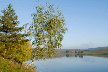 autumn colour: Leaves have begun to colour. Blue river is outline against the autumn trees.