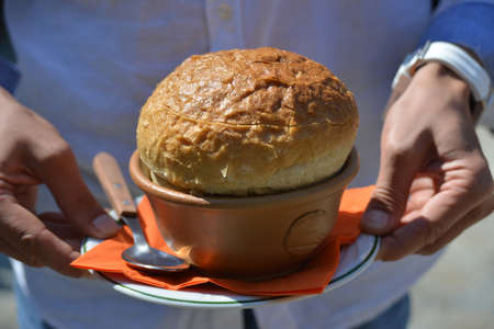 The  waiter serves soap in the bread. This is a  Rumanian traditional cuisine. Stock Photo