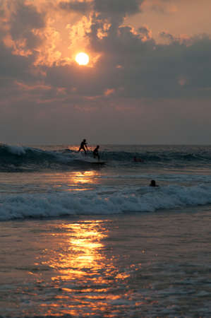 Surfers train themselves at sunset. Sundown is a good time for surf-riders.