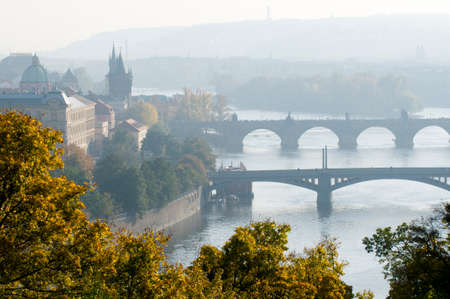 This is a morning view of the bridges on the Vltava River in Prague, Czech Republic. Yellow trees flavor the cityscape.