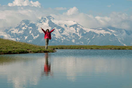 svaneti:  There is very beautiful mountain lake on the top of Mestia-Qoruldi (Svaneti region, Georgia - Caucasus Mountains). Woman dressed in bright red closes is situated against the mountains landscape. Stock Photo