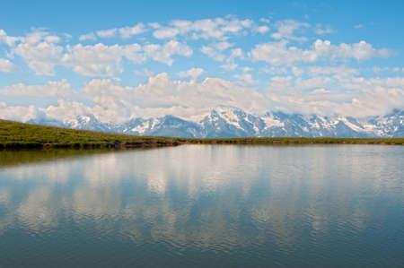 Clouds and blue sky reflect in the mountain lake. This is Caucasus Mountains - Georgia, Mestia region, Qoruldi lake.