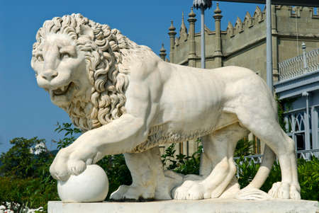 This marble lion sculpture is situated in Vorontsov Palace - Alupka, Crimea. The lion and palace are situated against the blue sky background.