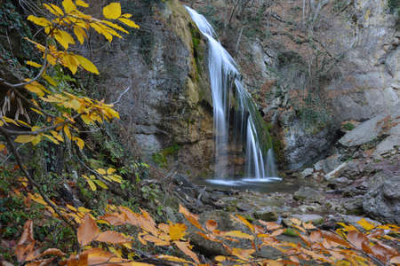Such view famous waterfall Djur-djur (Crimea) has in autumn. Yellow leaves are in the foreground. Stock Photo