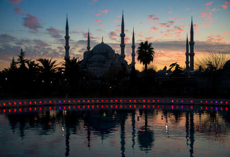 The silhouette of Mosque is situated against the sky background, water with reflection is in the foreground. The Sultan Ahmed Mosque (Istanbul, Turkey) is popularly known as the Blue Mosque for the blue tiles adorning the walls of its interior. Stock Photo - 31556467