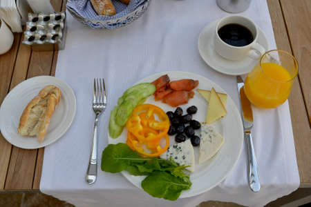 The breakfast concludes: olives, sweet pepper, cheese, roquefort, cucumber, salad, red fish (salmon) + orange juice and black coffee. Food is situated on the white dish and served with fork and knife. Stock Photo