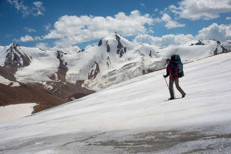 alpinism: The hiker moves along the glacier. Peaks and blue sky are in the background.