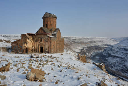Ruins of famous  Saint Gregory (Tigran Honents) church is surrounded with winter landscape. Ani is a ruined medieval Armenian city-site situated in the Turkish province of Kars, near the border with Armenia. Stock Photo