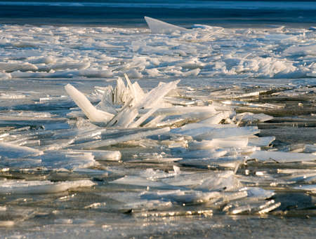 pileup: Winter: ice has covered the river. There is a pile-up of ice cakes in the foreground.