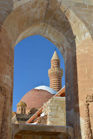agri: This is a view of Ishak Pasha Palace through the window of surrounded wall. The minaret and domes are situated against the blue sky background.