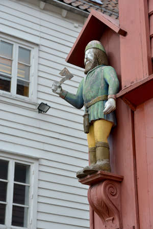 lumberman: Wood sculpture of   lumberman is decorated the house. Wood architecture is characteristic for old part of Bergen (Norway).