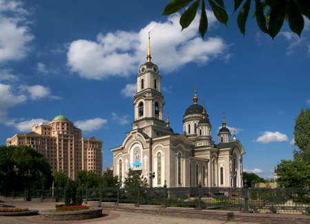 disputed: These are architecture of Donetsk city (Ukraine, disputed territory). Nativity of Christ church and modern building are situated against the blue sky background.