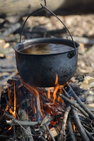Black pot with water is warming in fire. This is a story about  tourist life, cooking. photo