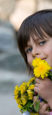 cuddles: Little girl cuddles yellow flowers in arms and smiles. This image is a good illustration for saying kids are a lot of fun.
