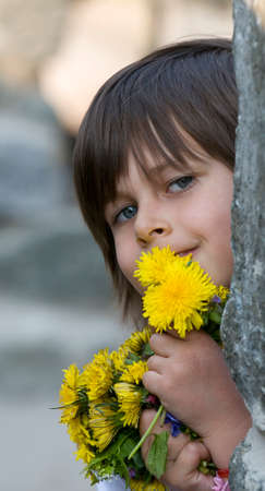 cuddles: Little girl cuddles yellow flowers (dandelions) in her arms and smiles. This image is a good illustration for saying kids are a lot of fun. Stock Photo