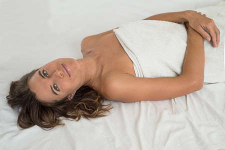 bedsheet: Young woman withoput clothes lye on white  bedsheet. Womans body is enveloped in  white towel. It may be a situation in SPA salon or after bathroom.