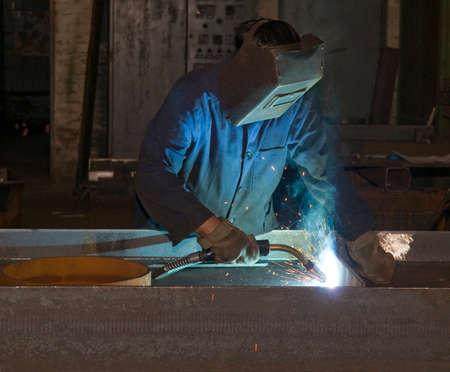 soldadura: Hombre de funcionamiento con el escudo casco en la cabeza es la soldadura de la construcción de acero. El trabajo duro en el departamento de producción.