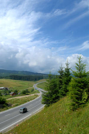 the carriageway: Gray minibus is moving along the asphalt road with carriageway marking. The road is surrounded with fields, meadows and forest. Fir-tree and grass are in the foreground, blue sky with clouds are in the backgrpound. Stock Photo