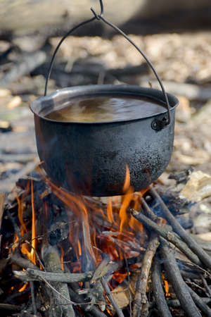 Black pot with water is warming in fire. This is a story about  cooking in walking holiday. photo