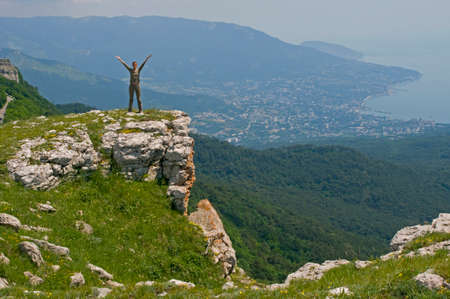 adventure holiday: Young woman stands on the edge of Ay-Petri Yayla (in Crimea Mountains). Yalta city, Mount Ayu-Dag and sea are in the background.