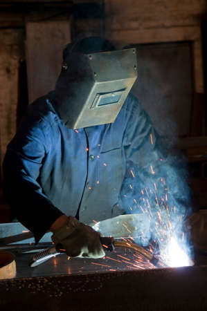 steel head: Working man with helmet shield on his head is welding steel construction. Heavy work in the production department.