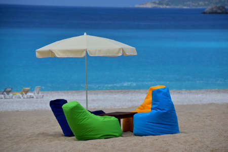 hassock: Bright multicolored seats and sunshade are situated on the beach. Blue sea is in the background. This is a sand equipped beach. Stock Photo