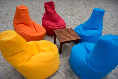 Place for relax on the sand beach. Multicolored seats looking like an armchair surround little wood table.