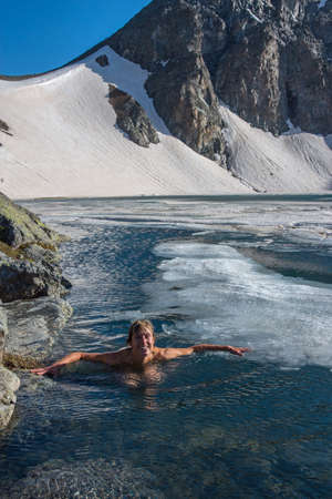 Happy woman swims in blue mountain lake with ice. Example of weathered people. Mount slope with snow is in background. Place - Deniz lake Kachkar, Turkey.