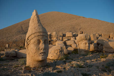 statue: Some of the statues near the peak of Mount Nemrut Turkey. West Terrace: head of Apollon and head of Goddess of Kommagene Tyche. Scene in the sunset sun.