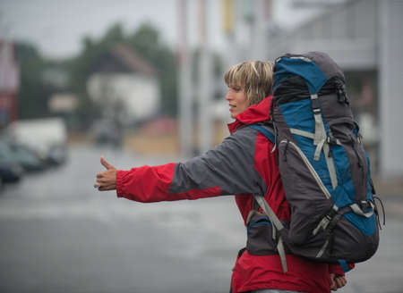 hitch hiker: Hitch-hiker with backpack - close-up. Woman is dressed in red parka.