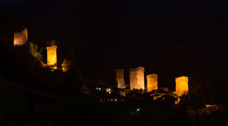 svaneti: Tradition svanetian towers illuminated in night. Mestia Svaneti, Georgia. Stock Photo