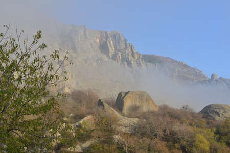 ghost rock: Rocks of Ghost valley Crimea are folded in mist. Autumn trees are in the foreground.