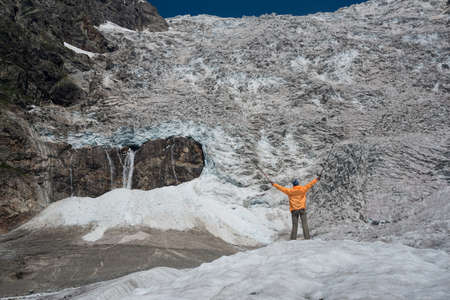 icefall: Tourist dressed in orange sweater looks at Adishi glacier also known as Lardaad. The drop of this icefall is more than 1000 m. Stock Photo