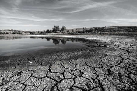 ephemeral: Drought. Chapped ground is in foreground. This is a coast of ephemeral impounded body. Black-and-white image.
