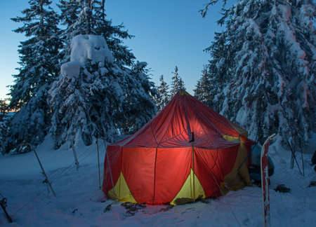 bivouac: Overnight stop bivouac in winter extreme travel. This is a ski travel. Big bright tourist tent against winter forest background.