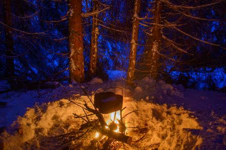 under fire: Escena de viajes de invierno. Dos ollas negras se están calentando en virtud del gran incendio. Fogata está rodeado con los árboles nevados. Sparks pistas se ven en la imagen.