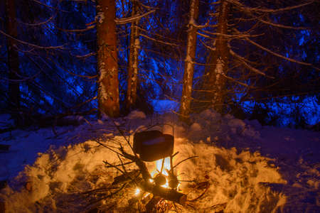 Scene from winter travel. Two black pots are heating under big  fire. Campfire is surrounded with snow covered trees.  Sparks tracks are seen in the image. Stock Photo - 48424106