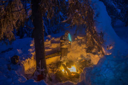 forest tea: Tourist cooks makes a tea near the fire. Two black pot heat under campfire. Winter travel scene in snow covered forest. Stock Photo