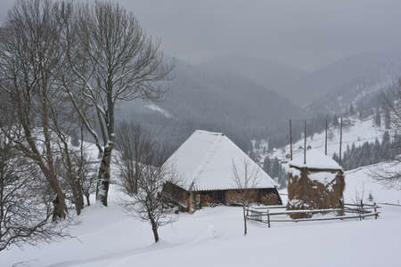 haymow: Little wood house and all space are covered with snow. The set of the hills in background. Stock Photo